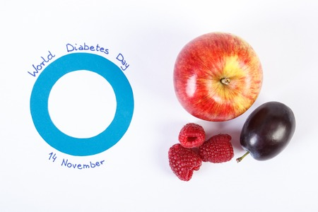 medical fight: Fresh ripe fruits and blue circle of paper, symbol of world diabetes day. White background Stock Photo