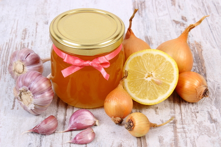 inmunidad: Fresh organic honey in glass jar, onion, garlic and lemon on old wooden background, healthy nutrition, strengthening immunity and treatment of flu
