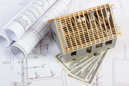 home expenses: Small house under construction, currencies dollar and electrical drawings and rolls of diagrams for project, concept of building home cost