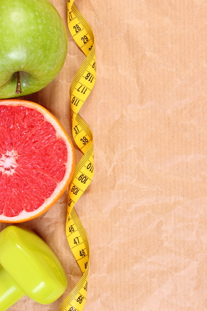 Fresh fruits, tape measure and dumbbells for using in fitness on old crumpled paper, concept of slimming, healthy lifestyles and nutrition, copy space for text