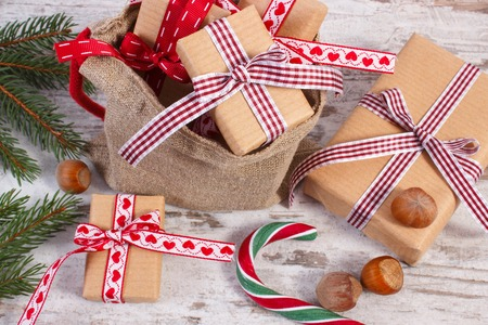 Gifts wrapped in old vintage paper tied colorful ribbon for Christmas, Valentines or other celebration, xmas candy cane and green spruce branches, wooden rustic background Stock Photo