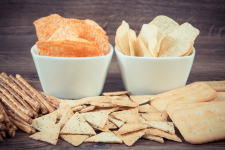 potato crisps: Vintage photo, Heap of crunchy salted potato crisps, breadsticks and cookies, concept of restriction eating unhealthy and salted food Stock Photo