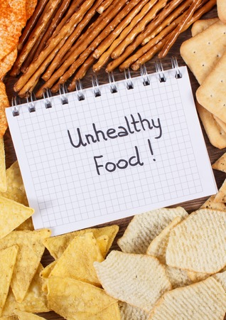 potato crisps: Inscription unhealthy food in notebook, crunchy potato crisps, breadsticks and cookies, concept of restriction eating salted food