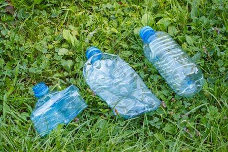botar basura: botellas aplastadas de plástico de agua mineral en la hierba en el parque soleado, el concepto de protección del medio ambiente, tirar basura del entorno