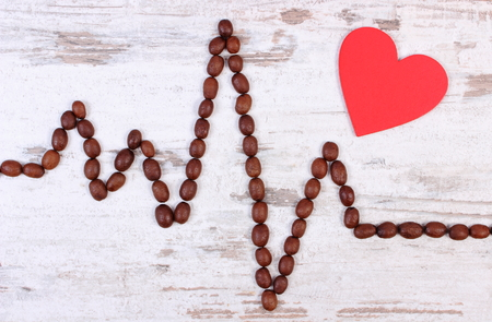 ecg heart: Electrocardiogram line of roasted coffee grains and red heart on rustic wooden background, ecg heart rhythm, medicine and healthcare concept