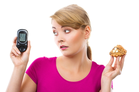 Shocked and worry woman holding fresh cupcake and looking at glucose meter with bad result of measurement sugar level, concept of diabetes, white background Stock Photo