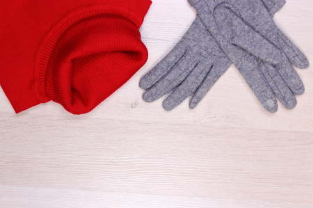 turtleneck: Womanly clothes on wooden plank, gloves and turtleneck sweater, copy space for text, warm clothing for autumn or winter Stock Photo