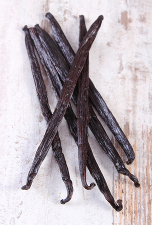 Fresh fragrant vanilla sticks pods on old rustic wooden board, seasoning for cooking or baking