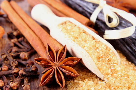 granule: Brown sugar cane on spoon, fresh fragrant vanilla pods and cinnamon sticks, star anise and cloves, seasoning for cooking or baking