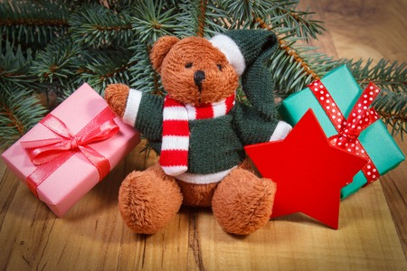 Fluffy teddy bear with red wooden star and wrapped gifts for Christmas or other celebration