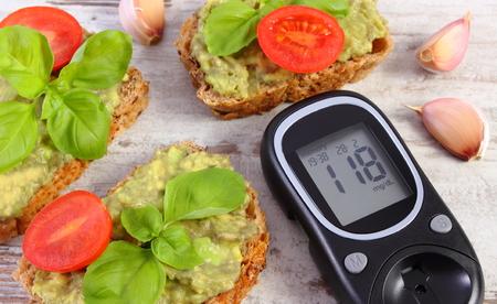 Glucómetro con resultado de nivel de azúcar en la medición y sándwiches recién con la pasta de aguacate, el concepto de la diabetes, la alimentación sana, la nutrición y los ácidos grasos omega Foto de archivo