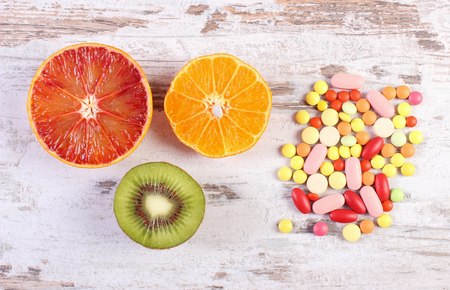 medical choice: Fresh natural fruits and medical pills, tablets and capsules on rustic wooden background, choice between healthy nutrition and supplements, healthy lifestyle Stock Photo