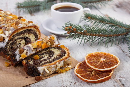 strudel: Poppy seeds cake, black coffee and spruce branches on rustic board, dessert and decoration for Christmas, rolled up traditional polish poppy pie Stock Photo