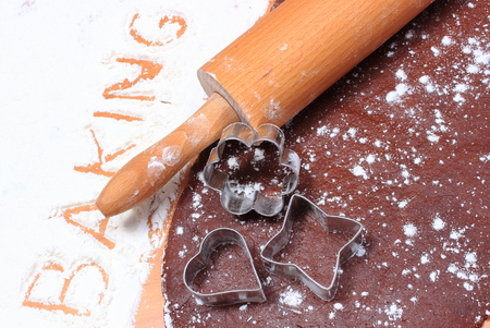 pastry cutters: Cookie cutters and rolling pin lying on dough for cookies, concept of baking Stock Photo