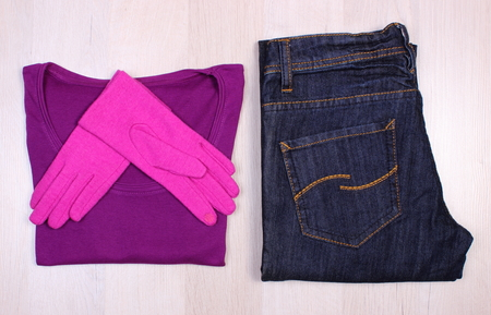 warm shirt: Pair of gloves, sweater or shirt and pants for woman on wooden board, womanly accessories, warm clothing for autumn or winter