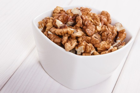 containing: White bowl with walnuts containing zinc and dietary fiber on white boards, natural sources of minerals, healthy lifestyle and nutrition