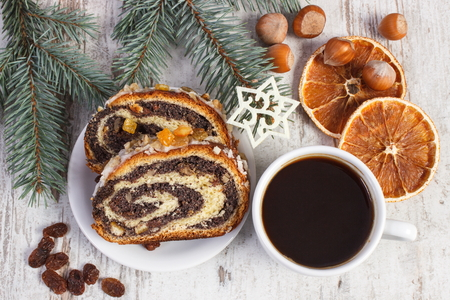 strudel: Poppy seeds cake on plate, cup of coffee and spruce branches, dessert for Christmas, rolled up traditional polish poppy pie Stock Photo