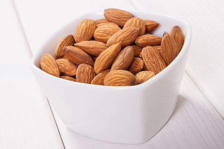 containing: White bowl with almonds containing zinc and dietary fiber on white boards, natural sources of minerals, healthy lifestyle and nutrition