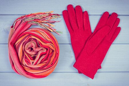 Vintage photo, Woolen gloves and colorful shawl for woman on boards, warm clothing for autumn or winter, womanly accessories Stock Photo