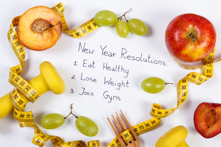 New year resolutions or goals on white background, fresh fruits, dumbbells and tape measure with wooden fork, healthy food and lifestyle