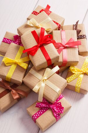 Wrapped gifts with colorful ribbons for Christmas, Valentine, birthday or other celebration lying on white boards