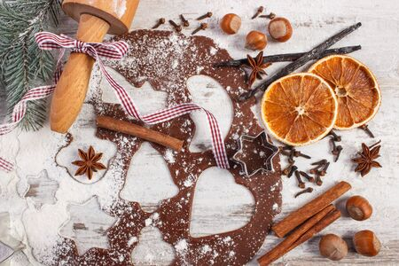 Dough for Christmas cookies with spice and ingredients for baking gingerbread, green spruce branches on old rustic board Stock Photo