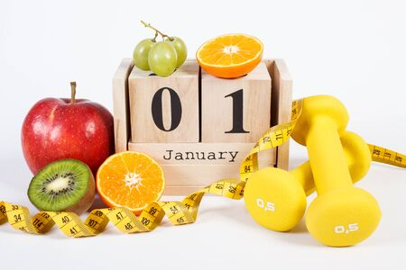 January 1 on cube calendar, fresh fruits, dumbbells and tape measure, new years resolutions of healthy lifestyle Stock Photo