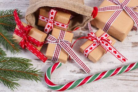 Gifts wrapped in old vintage paper tied colorful ribbon for Christmas, Valentines or other celebration, Christmas candy cane and green spruce branches Reklamní fotografie