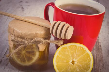 warming therapy: Vintage photo, Lemon with honey in glass jar, fresh lemon and cup of hot tea on old rustic board, healthy food, strengthening immunity and alternative therapy Stock Photo