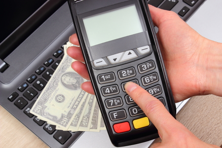 personal identification number: Hand of woman using payment terminal, enter personal identification number, credit card reader, currencies dollar on laptop, finance and banking concept
