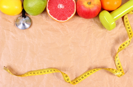 Fresh fruits, tape measure, medical stethoscope and dumbbells for fitness on old crumpled paper, concept of slimming, healthy lifestyles and nutrition, copy space for text Stock Photo