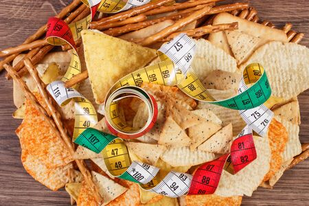 gressins: Tape measure with crunchy salted potato crisps, cookies and breadsticks on rustic board, concept of slimming, restriction eating unhealthy and salted food Banque d'images