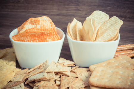 Vintage photo, Heap of crunchy salted potato crisps and cookies, concept of restriction eating unhealthy and salted food