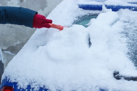 Hand of woman using brush and remove snow and ice from car and windscreen, concept of transportation and winter
