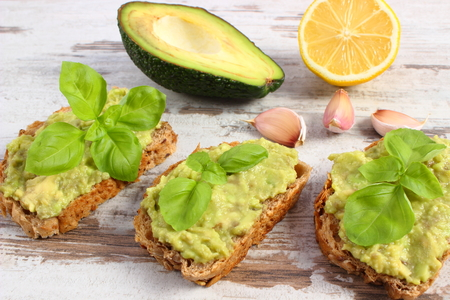 freshly prepared: Ingredients and freshly prepared sandwiches with paste of avocado, rye bread, lemon, garlic, basil, concept of healthy food, nutrition and omega fatty acids
