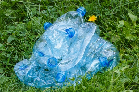 crushing: Crushed plastic bottles of mineral water on grass in park, concept of environmental protection, littering of environment Stock Photo