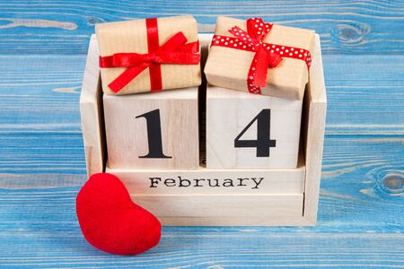 February 14 on cube calendar, wrapped gifts with ribbon and red heart, decoration for Valentines day Stock Photo