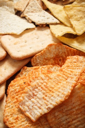 Heap of salted potato crisps with peppers and cookies, concept of restriction eating unhealthy and salted food Stock Photo