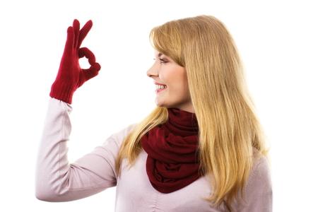 Šťastná žena na sobě vlněné rukavice a šátek, ukazující znamení ok, schválení nabídky nebo situace, ukazující pozitivní lidské emoce Reklamní fotografie