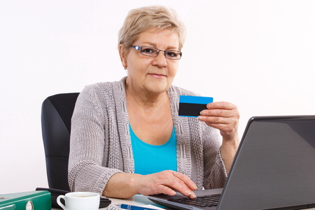 over paying: Senior woman, an elderly pensioner with credit card and laptop paying over internet for utility bills or online shopping, surfing internet, typing on computer keyboard Stock Photo