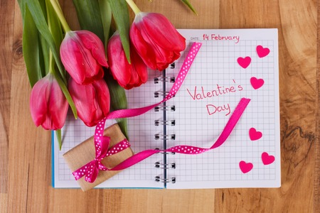 Date of February 14 written in notebook or calendar, fresh tulips, wrapped gift with ribbon and hearts of paper, decoration for Valentines Day