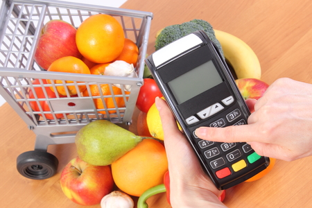 personal identification number: Hand using payment terminal, enter personal identification number, credit card reader and fresh fruits and vegetables with plastic shopping carts, cashless paying for shopping