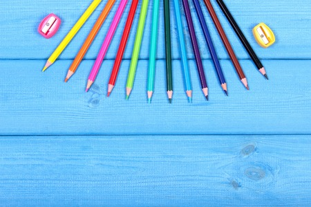space for text: Colorful crayons and sharpener on blue boards, school supplies and accessories, copy space for text or inscription Stock Photo