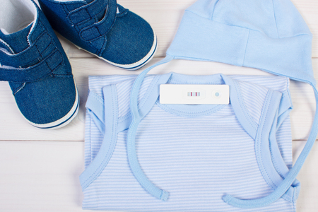 extending: Pregnancy test with positive result and clothing for newborn on boards, concept of extending family and expecting for baby Stock Photo