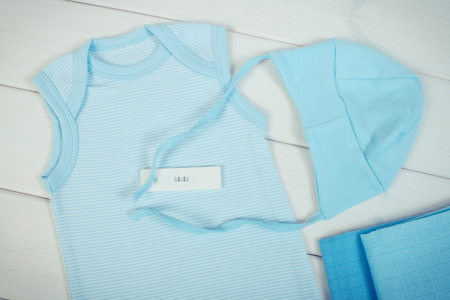extending: Vintage photo, Pregnancy test with positive result and clothing for newborn on boards, concept of extending family and expecting for baby