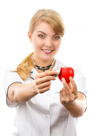 Smiling woman doctor cardiologist in white apron with stethoscope examining red heart, healthcare and medicine concept, white background