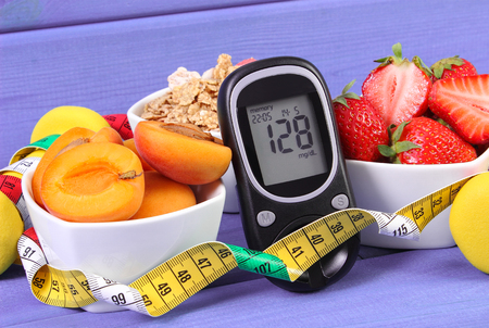 Glucose meter with result of measurement sugar level, healthy food and tape measure, concept of diabetes, slimming, healthy lifestyle Stock Photo