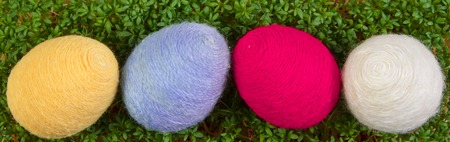 Easter eggs wrapped woolen string and fresh green cuckooflower cress, decoration for Easter