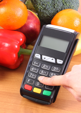personal identification number: Hand of woman using payment terminal, enter personal identification number, credit card reader and fresh fruits and vegetables