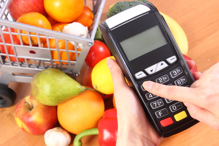 personal identification number: Hand of woman using payment terminal, enter personal identification number, credit card reader and fresh fruits and vegetables with plastic shopping carts